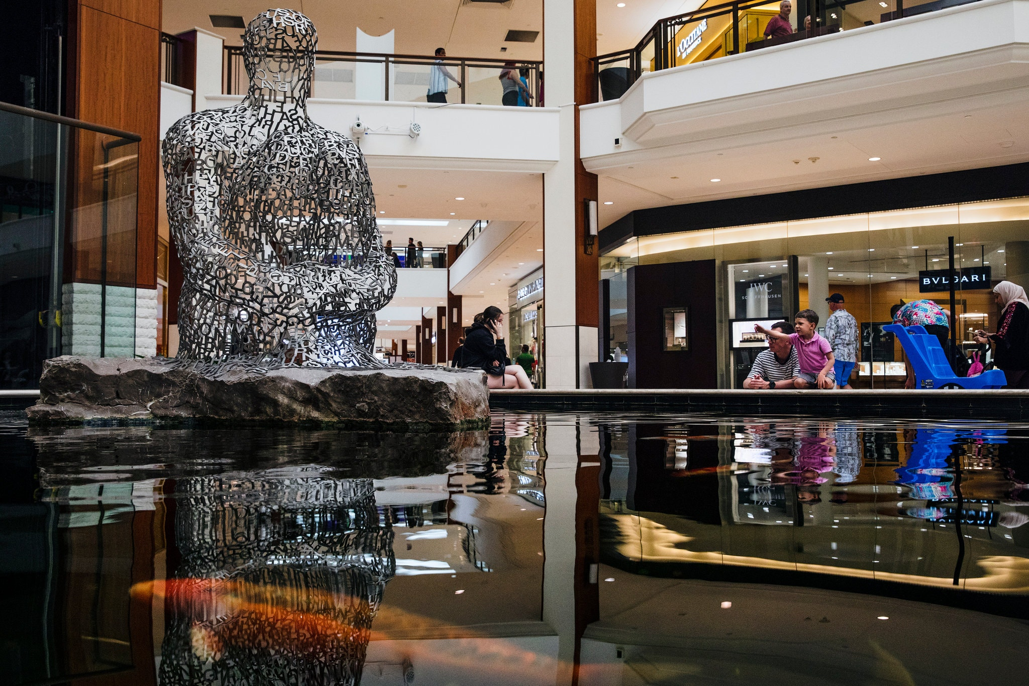 A koi pond and a sculpture by Jaume Plensa on the lower level of the mall.Credit...Scott McIntyre for The New York Times